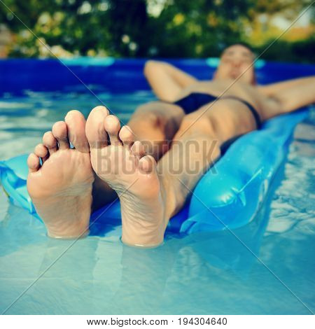young caucasian man wearing a blue swimsuit relaxing in an air mattress in a portable swimming pool placed in the backyard