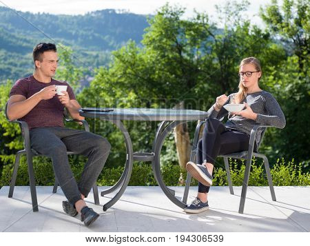 young beautiful handsome couple enjoying morning coffee and breakfast in front of their luxury home villa