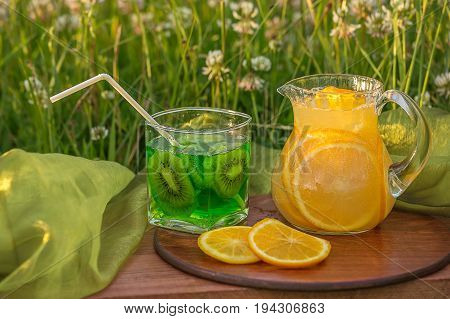 Two glass jars with lemonade on a wooden stand on the grass. Soda in a jar with a lid. Breakfast on the grass.