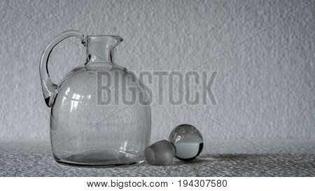 a vintage clear glass pitcher with its  stopper casting a slight shadow against a white background, with space for overprinting text