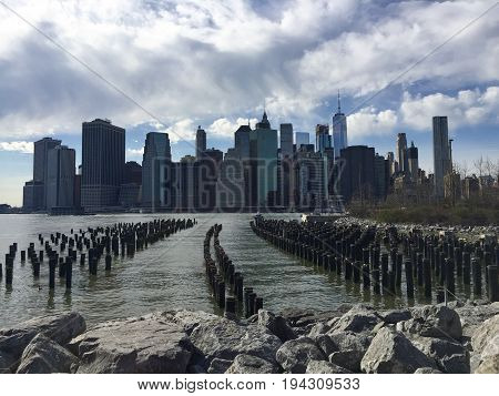 Buildings in Manhattan,wooden logs and rocks with East river and cloudy sky
