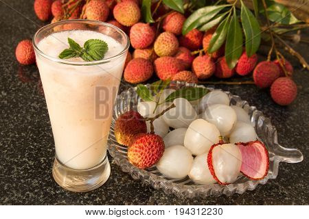 Litchi juice in a glass. Fresh juicy lychee fruit on a glass plate. Organic leechee sweet fruit. Organic fruit concept. Exotic tropical litschi berry. Peeled lychee fruit.Selective focus.