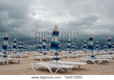 Bad weather. Closed beach sunshades against gray sky background.