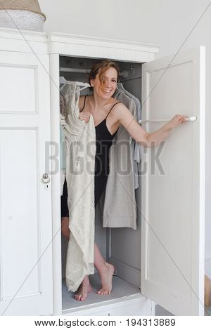 A girl in a black dress peeks out from behind the closet door studio photography