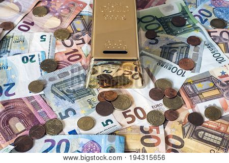 savings Cash money concept euro banknotes of all sizes and cent coins on desk piggy bank gold bar shape save