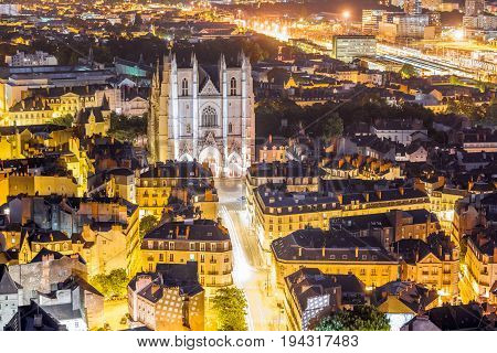 Aerial cityscape view with illuminated buildings and saint Pierre cathedral in Nantes city during the night in France