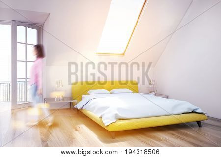 Woman in a white attic bedroom with a wooden floor a narrow window a yellow bed and an open balcony door. Close up. 3d rendering mock up toned image