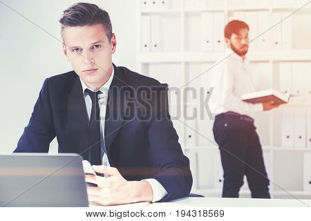Two young businessmen working in a white office. One is looking at the viewer sitting at his table. The second is readering a book. Toned image