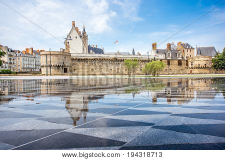 View on the castle of Dukes of Brittany with water mirror fountain in Nantes city in France