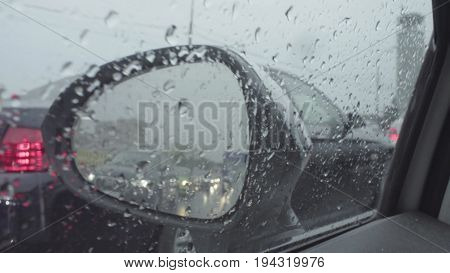 Point of view in car's rearview mirror on the city street. Rain in Moscow, may, POV