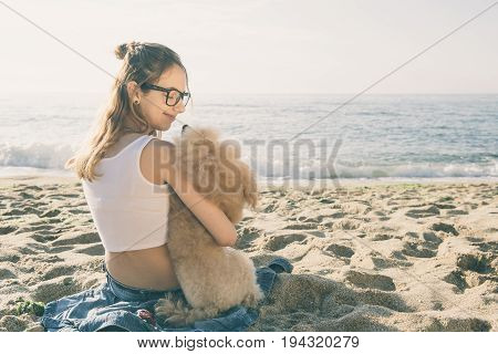 Young girl is resting with a dog on the sea.