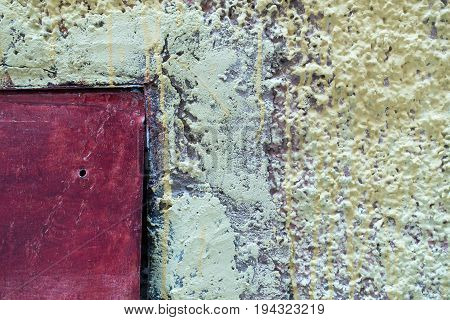 Very rough textured cement wall with metal door in yellowish greenish white and purple colors as background.