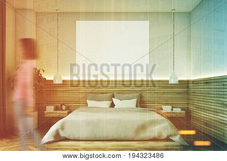 Woman in a modern bedroom interior with wooden walls and floor two bedside tables a double bed and a poster hanging above it. 3d rendering mock up toned image