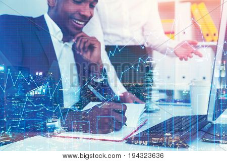 Portrait of a cheerful African American businessman writing in his planner and listening to a colleague standing near his table. Graphs. Toned image double exposure