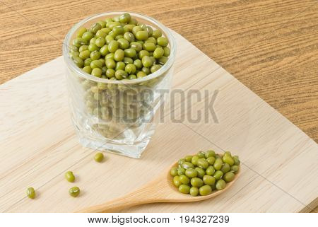 Cuisine and Food Raw and Uncooked Mung Dried Beans in A Wooden Spoon and A Tumbler on Wooden Table.