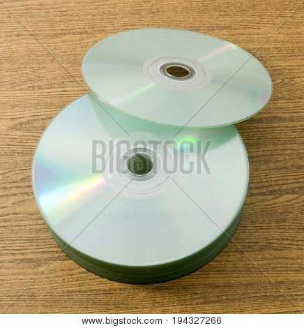 Stack of CD or DVD Compact Disc on A Wooden Table.