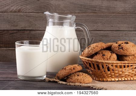 jug and glass of milk with oatmeal cookies in a wicker basket on a wooden background.