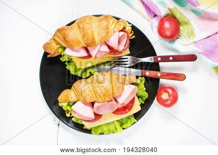 Light and hearty spring breakfast. Croissant with ham cheese fresh tomatoes on a white stone table. Top view