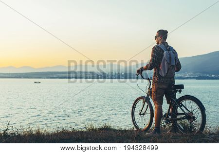 Young Man Cyclist Standing With Bike On Coast And Enjoying View Of Sunset Vacation Traveling Destination Resting Concept