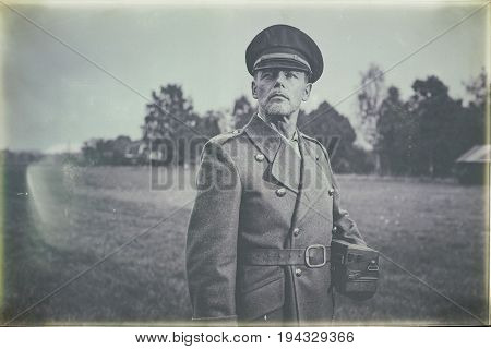 Antique Black And White Photo Of 1940S Military Officer Standing In Field With Phone.