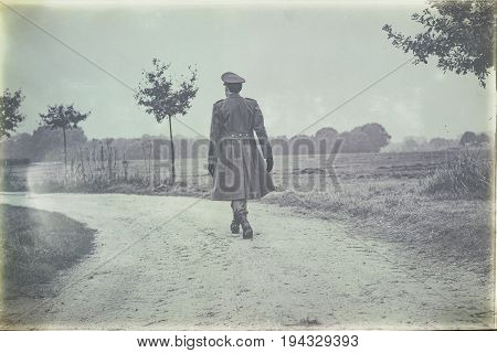 Antique Black And White Photo Of 1940S Military Officer Walking On Rural Road. Rear View.