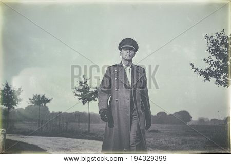 Antique Black And White Photo Of 1940S Military Officer Walking On Rural Road.