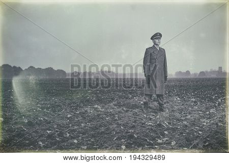 Antique Black And White Photo Of Patrolling 1940S Military Officer Standing On Farmland.