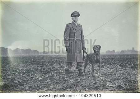 Antique Black And White Photo Of Patrolling 1940S Military Officer Standing With Dog On Farmland.