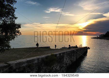 PULA/CROATIA - 7 JULY 2017: People watching sunset on a pier in Verudela, Istria