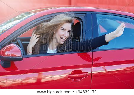 Portrait of young and beautiful Caucasian business lady with long hair wearing formal suit on the wheel of red modern car hanging and flirting with her college while parking at the office.