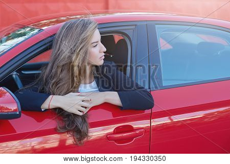 Portrait of young attractive Caucasian business lady with long hair wearing formal suit on the wheel of red modern car looking afar waiting her boss to come to the office.