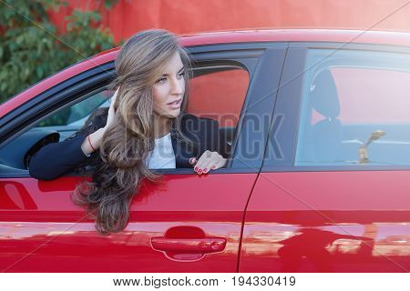 Portrait of young attractive Caucasian business lady with long hair wearing formal suit on the wheel of red modern car looking for somebody waiting for college to come to the office together