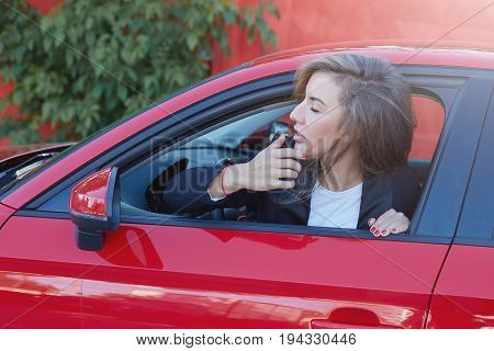 Portrait of young attractive Caucasian business lady with long hair wearing formal suit on the wheel of red modern car looking afar waiting her boss to come to the office. Picture in motion.