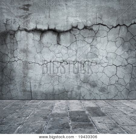 Grungy distressed stone wall and floor with large cracks.