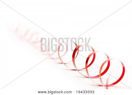 Curled coil of red ribbon fading in to a bright white background.
