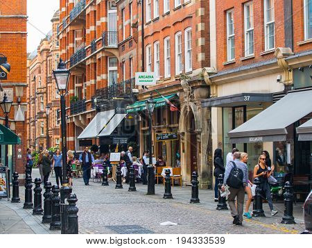 London, UK - September 8, 2016: Group of young people chatting next to the Cafe entrance at the Kensington hight street.