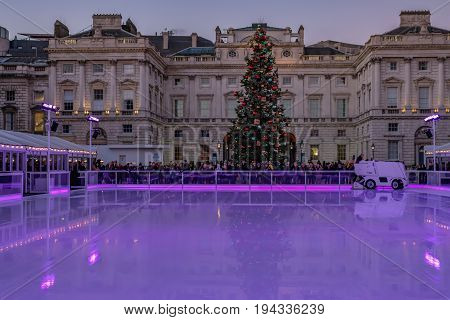 London England UK - December 29 2016: Ice-skating rink ready for the next session at Somerset House. An evening shot with illumination and Christmas tree.