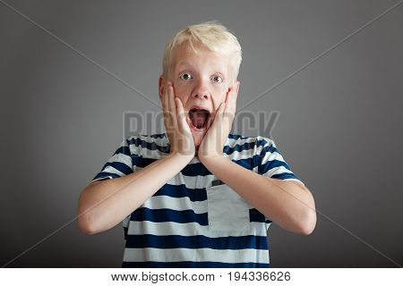 Shocked Teen In Striped Shirt With Hands On Cheeks