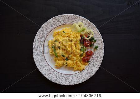 Fresh scrambled eggs with vegetables. Domestic eggs for breakfast. Preparing eggs.