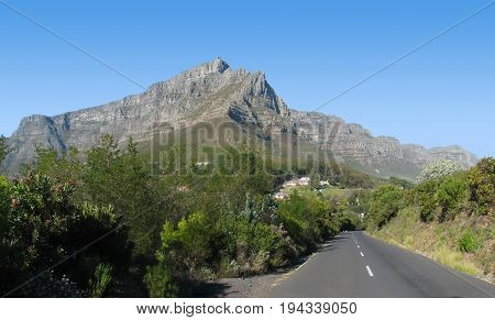 FROM CAPE TOWN, SOUTH AFRICA, WITH ROAD IN FORE GROUND AND TABLE MOUNTAIN IN THE BACK GROUND 26degh