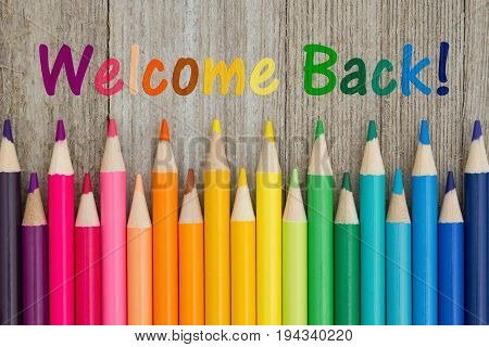 Welcome back text with colorful pencil crayons on a weathered wood