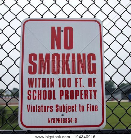 A no smoking sign hangs on a fence at a local high school