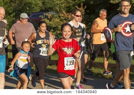 Babylon NY USA - 26 June 2017: Runners enjoying their race and waving to the camera while wearing super hero costumes at the Belmont Lake Summer Series 5K race.