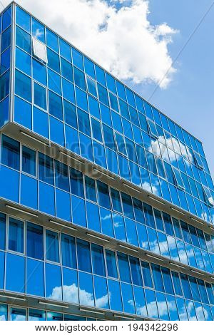 Facade of a modern building. Glass Windows reflected the sky and clouds. Blue gamma.
