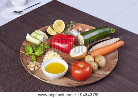 Ingredients vegetables for soup with pesto sauce and basil on a wooden plate. Stock image.
