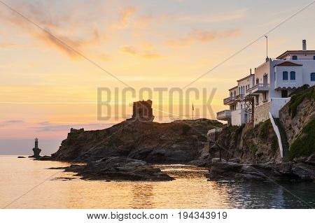 Castle and lighthouse in Chora of Andros island early in the morning.