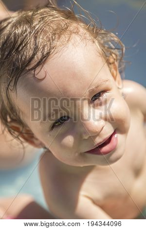 Portrait of a beautiful smiling child in an inflatable pool over summer outside in the garden