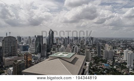 Aerial drone view of helipad isolated on top of the skycraper in Bangkok city during cloudy day