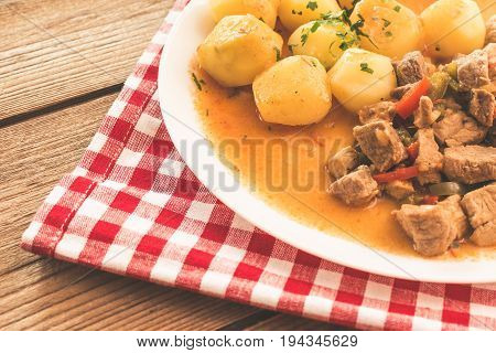 Goulash with meat, vegetables and potatoes on wooden table.