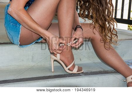 Close up of legs in tan pantyhose and open toe heels on building steps.